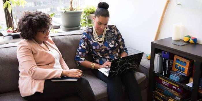 Twee vrouwen achter een laptop op de bank