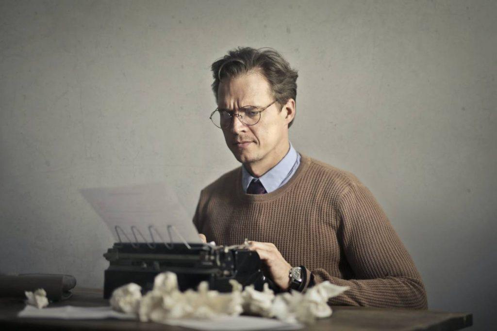 Man met bril achter typmachine verricht SEO-onderzoek