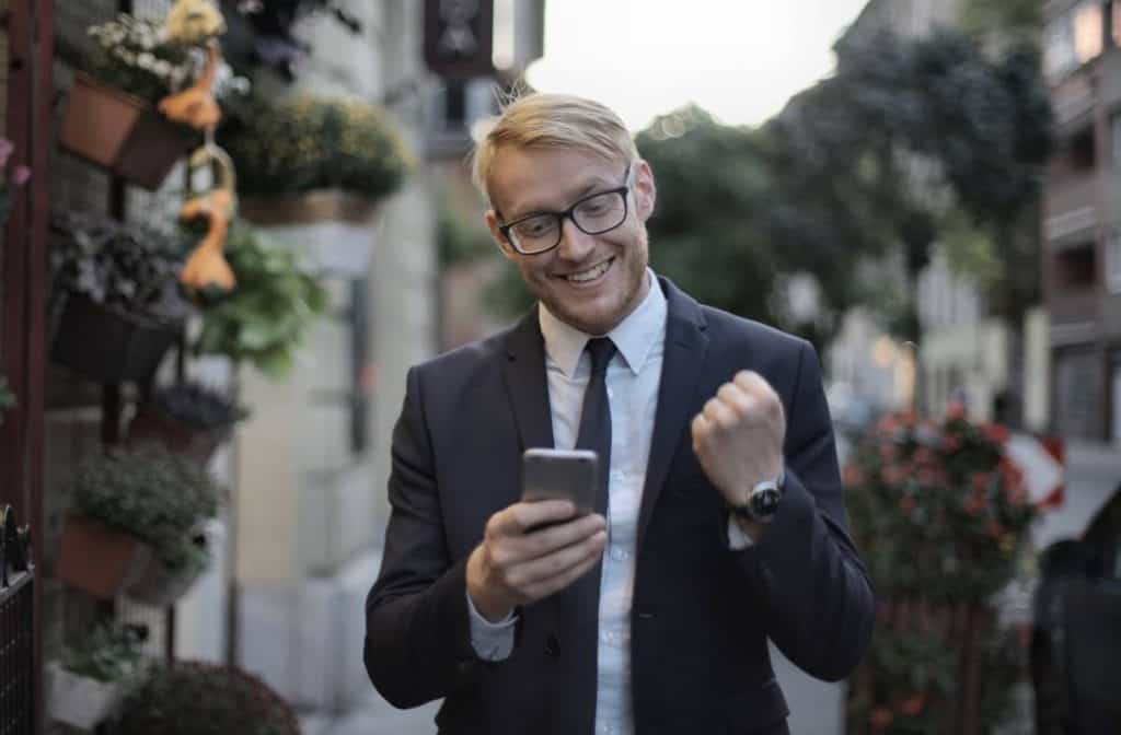 Man is blij met bericht op zijn telefoon