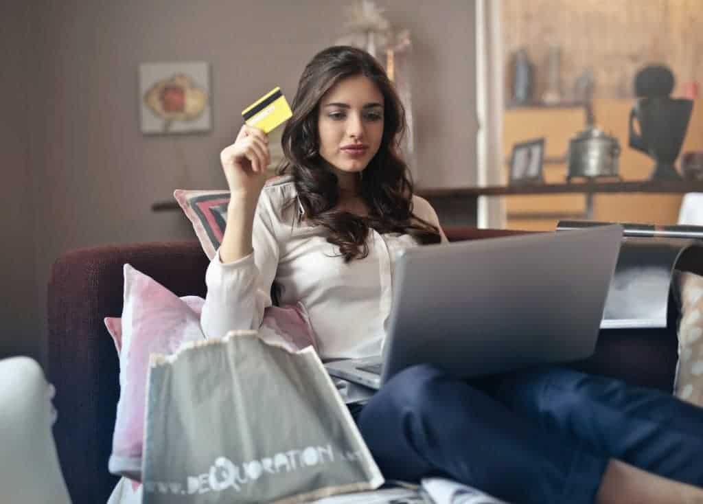 vrouw met pinpas doet aankoop op laptop