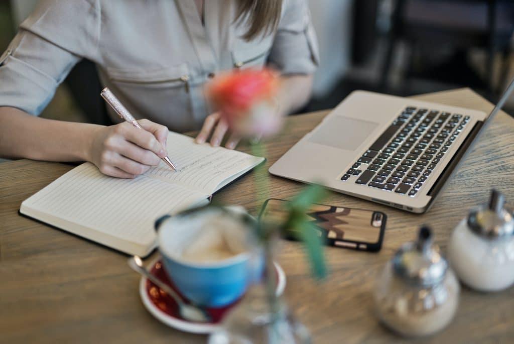 Vrouw schrijft in notitieblokje